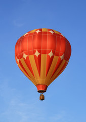 Red and orange hot air balloon in the blue sky.