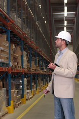 supervisor in hardhat checking inventory in warehouse