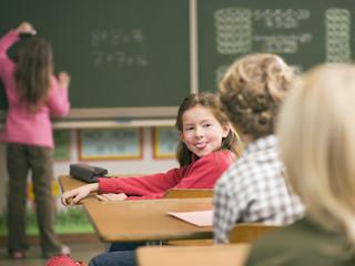 Kinder in Klassezimmer, Mädchen Zunge heraus strecken