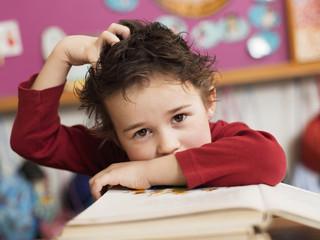 Junge sitzen am Schreibtisch mit Buch, Hand im Haar, Portrait, close-up