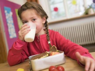 Mädchen sitzen Schreibtisch, trinken Glas Milch, Portrait