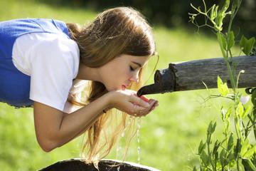 Frau jung trinken Wasser aus Brunnen