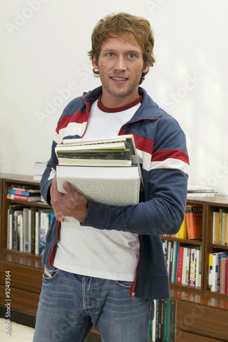Young man standing with holding books, portrait