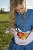 Girl (7-9) carrying apples in apron, close-up