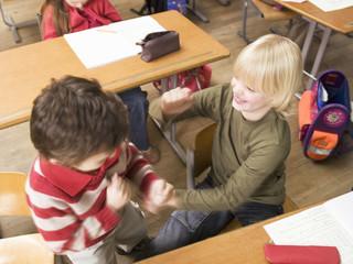 Jungen streiten in Klassenzimmer