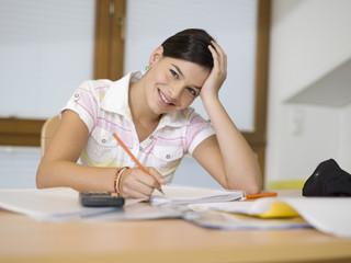 Junge Frau sitzt am Schreibtisch, Schreiben