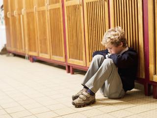 Junge sitzen vor Spind, Seitenansicht