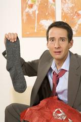 Mann sitzen auf dem Sofa, Socken halten