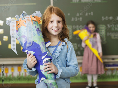 Girl (6-7) holding school cone, smiling, portrait
