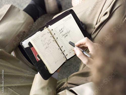Businessman holding time planner, overhead view, close-up