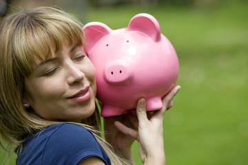Beautiful casual woman smiling and holding piggybank - outdoors