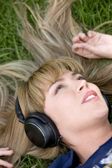 Girl listening to music looking relaxed - outdoors