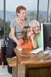 grandparents and granddaughter with computer at home