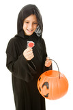 Adorable little trick or treater about to eat a lollipop poster