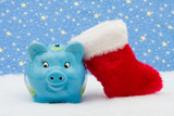 Piggy bank and red stocking sitting on snow, Christmas savings