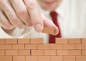 hombre de negocios construyendo un muro