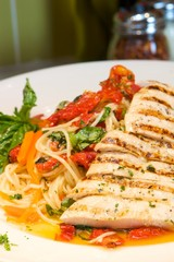 An image of pasta with grilled chicken, basil and bell peppers