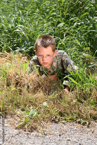 young boy in cammoflage crawling out of the grass