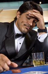 Stressed poker player contemplating his few chips in a casino