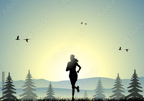 A young girl running at sunset in a forest