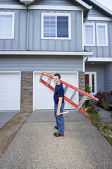 man standing in front of house holding ladder. Vertical