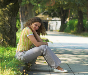 Young girl is sitting on kerb in the park