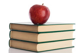 A red apple on top of three books on a white background