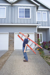 man standing in front of house holding ladder  Vertical.