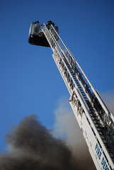 Ladder truck with fireman at top battles a blaze.