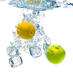ice cubes, lemon and apple are dropped into water