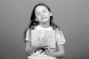 Young girl looking calm while holding Bible
