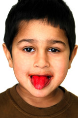 An handsome Kid showing his tongue after eating a candy