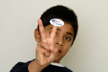 A kid holding the vote sign symbol of election in America