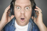 Shocked Man Wearing Headphones against a grey background. poster