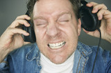 Shocked Man Desperately Trying To Take Off Headphones poster