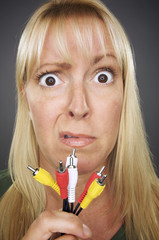 Confused Woman Holds Electronic Cables - on Grey Background.