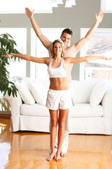 Young man and woman woman doing exercise  in the sunny room.