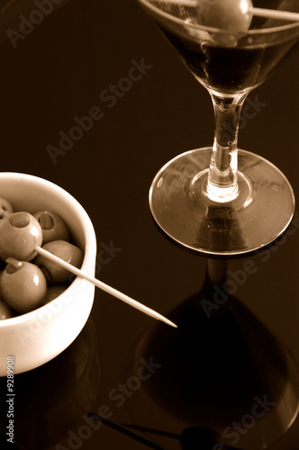Cocktail drink with bowl of Olives on reflective background