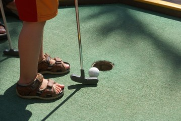 putting a ball into a hole of crazy golf