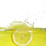 Fototapety Image of lemon slice falling into juice
