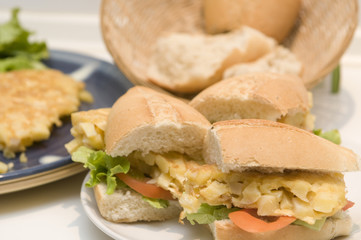 a hand making an spanish omelet sandwich with potatoes