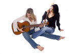 two female guitarists practicing while sitting on the floor