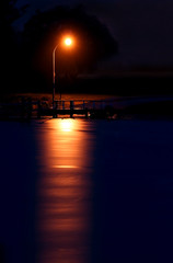 A street light reflecting over the ocean at night