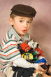 Young boy with all his toy cars in his arms