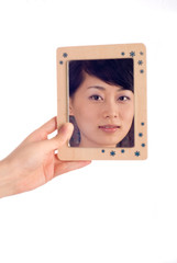 Love lady looking at mirror with wooden boarder