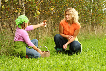 Mother and daughter picking mushrooms, showing big one