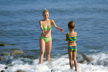 Mother and  daughter a standing in a sea