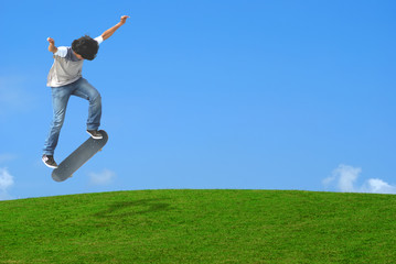 Young skater jumping over a green  hill.