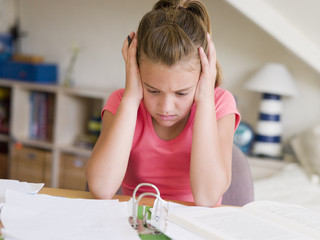 Young Girl Doing Her Homework With Her Head In Her Hands