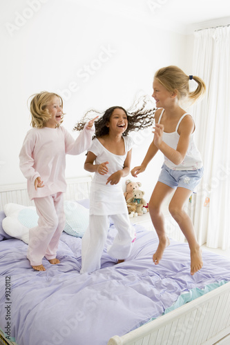 Three Young Girls Jumping On A Bed In Their Pajamas